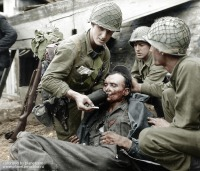 Франция - American soldiers give water to a wounded German soldier in Limay, France in 1944