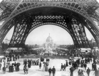 Париж - Paris Exposition, view from ground level of the Eiffel tower with Parisians promenading Франция